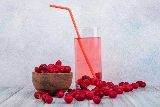 Вид сбоку свежих красных ягод кизила на деревянной миске с ягодным соком кизила на стакане с ягодами кизила, изолированными на сером фоне