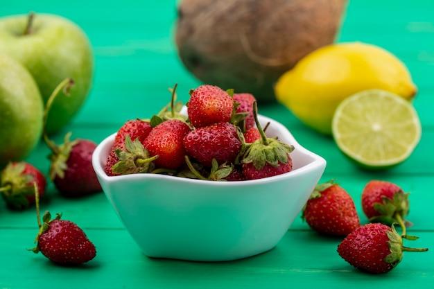 Вид сбоку свежей красной клубники на белой миске с лимоном и яблоком на зеленом фоне