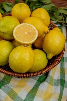Вид сбоку свежих спелых лимонов в плетеной корзине с зелеными листьями на клетчатой ткани