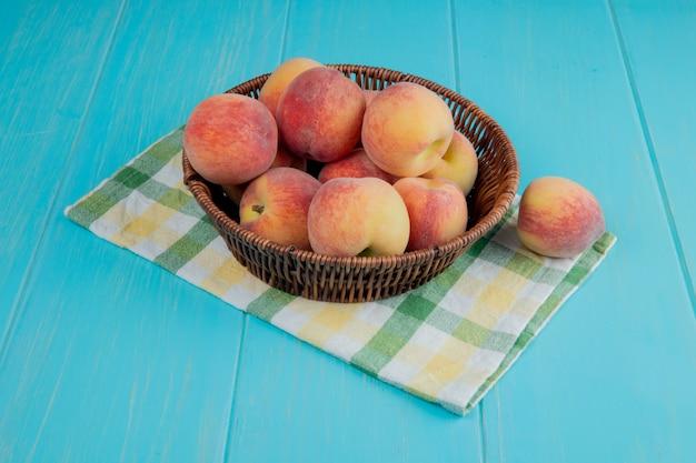 青い木製のテーブルの枝編み細工品バスケットで新鮮な熟した桃の側面図