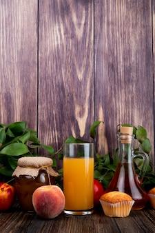 Вид сбоку свежих спелых персиков с кекс персиковый джем в стеклянной банке и персиковый сок в стакан на деревенском дереве