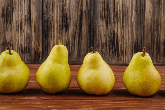 木製の背景の行に新鮮な熟した梨の側面図