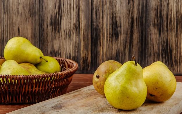 Вид сбоку свежих спелых груш в плетеной корзине и на разделочную доску на деревянном фоне