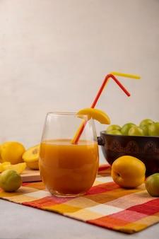 Вид сбоку свежего сладкого желтого персикового сока на стакане со свежими персиками с зелеными алычами на банте на белом фоне