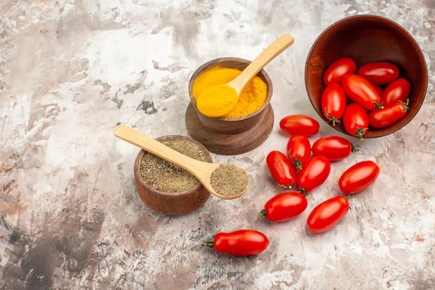 회색 배경에 있는 작은 냄비와 다양한 향신료에서 떨어진 신선한 토마토의 측면