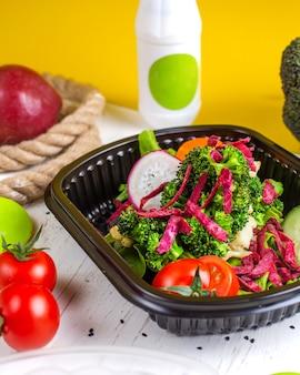 Вид сбоку салат из свежих овощей с редькой и красной капустой, морковью и брокколи в коробке доставки на столе