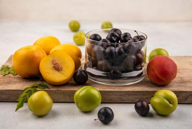 Вид сбоку свежих желтых персиков на деревянной кухонной доске с темно-фиолетовыми стружками на стеклянной миске на белом фоне
