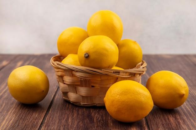 白と白の壁の上の木製のテーブルで隔離されたレモンとバケツの上の新鮮な黄色の皮を剥がれたレモンの側面図
