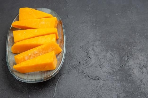 검정색 배경에 오른쪽에 파란색 접시에 신선한 노란색 슬라이스 치즈의 측면보기