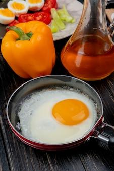 木製の背景にオレンジ色の唐辛子とリンゴ酢とフライパンで目玉焼きの側面図