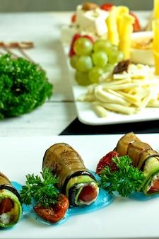 Вид сбоку жареных рулетиков из баклажанов с чесноком и сливочным сыром на блюде