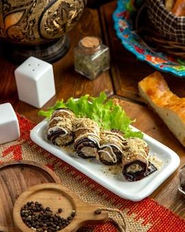 Вид сбоку жареные рулетики из баклажанов с грецкими орехами и майонезом на тарелку на деревянном столе
