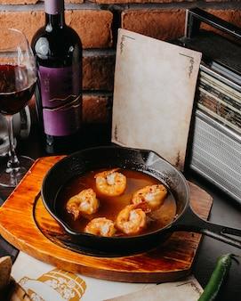 黒い鍋にエビのソース炒めの側面図
