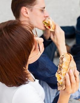 屋外でハンバーガーを食べる友人の側面図