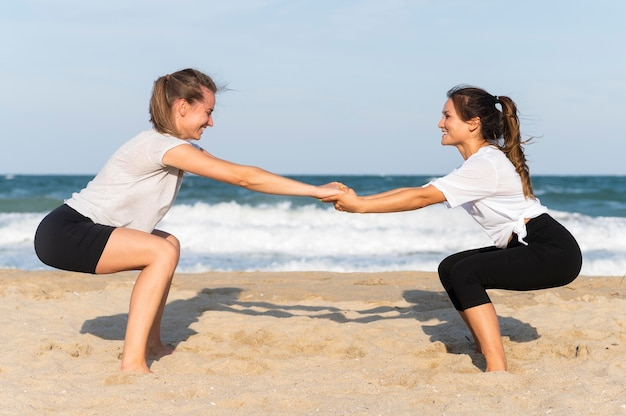 Вид сбоку друзей, тренирующихся вместе на пляже