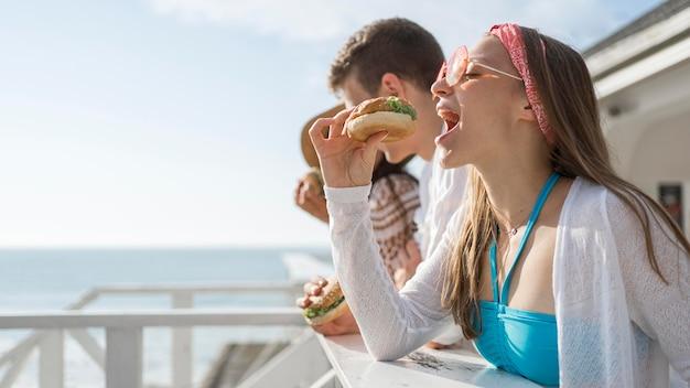 屋外で一緒にハンバーガーを食べている友人の側面図