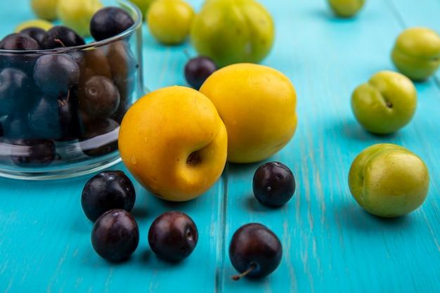 青い背景にブドウの果実のボウルとブドウの果実プラムとネクタコットとしての果物の側面図