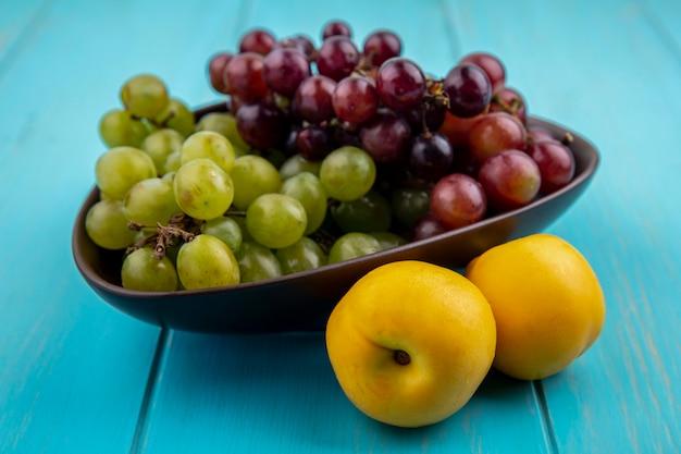青い背景の上のネクタコットとブドウのボウルとしての果物の側面図