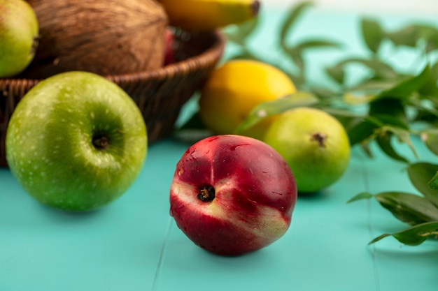 Вид сбоку на фрукты, такие как персик, яблоко, груша, лимон с корзиной кокосовых бананов и листьев на синем фоне