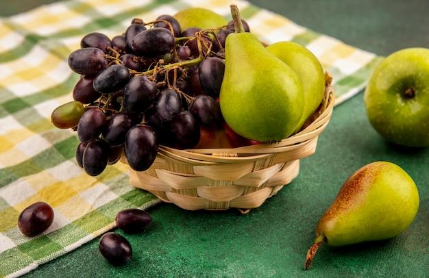 Вид сбоку на фрукты, персиковый виноград и грушу в корзине на клетчатой ткани с яблоком на зеленом фоне
