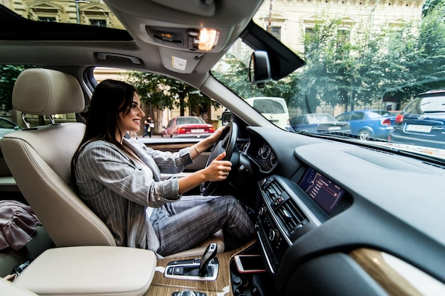 차를 운전 좌절 된 젊은 비즈니스 우먼의 측면보기.