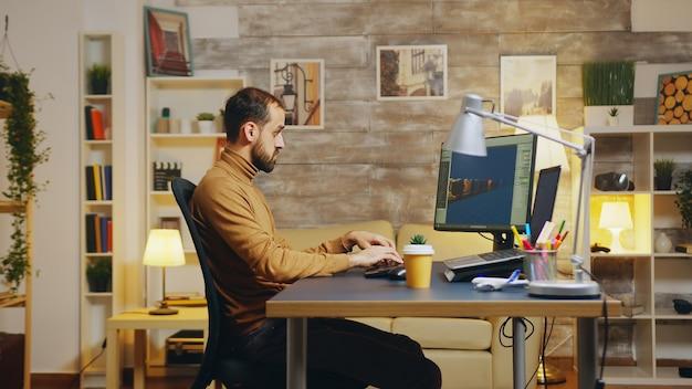 새 인터페이스에서 홈 오피스에서 작업하는 게임 개발자의 측면 보기.