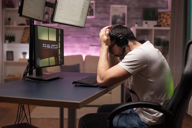 Вид сбоку игры для человека с наушниками, играющего в шутеры в комнате с неоновым светом.