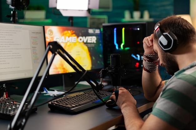 스트리밍 채팅이 열린 상태에서 헤드폰을 끼고 온라인 비디오 게임을 하는 스트리머 남자의 게임 오버 측면 보기. 전문 콘솔을 사용하여 가정의 게임룸에서 강력한 컴퓨터에서 사이버 수행