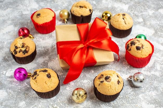 Вид сбоку на подарок с красной лентой среди свежеиспеченных вкусных маленьких кексов и декоративных аксессуаров на ледяном столе