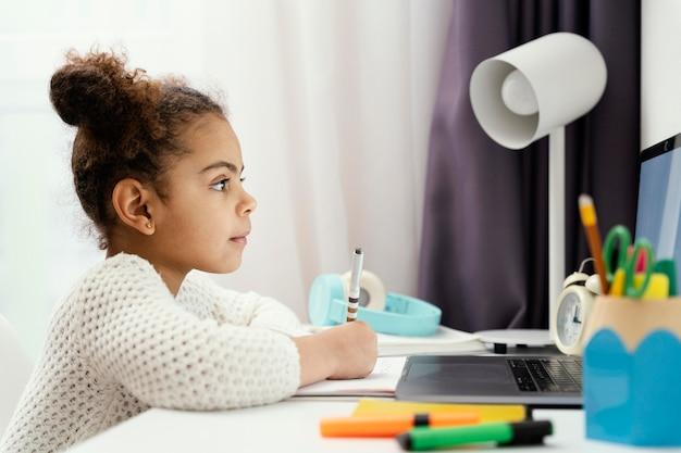 노트북을 사용하여 집에서 온라인 학교에 다니는 소녀의 측면보기
