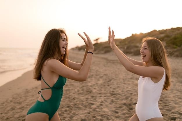 해변에서 하이 파이브 제스처를 인사하는 여자의 모습