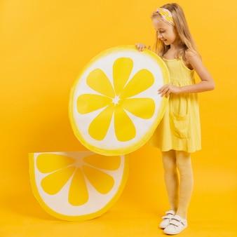 レモンスライスの装飾を保持している女の子の側面図