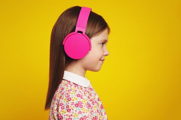 Вид сбоку на девочку с розовыми наушниками, улыбающуюся во время прослушивания музыки