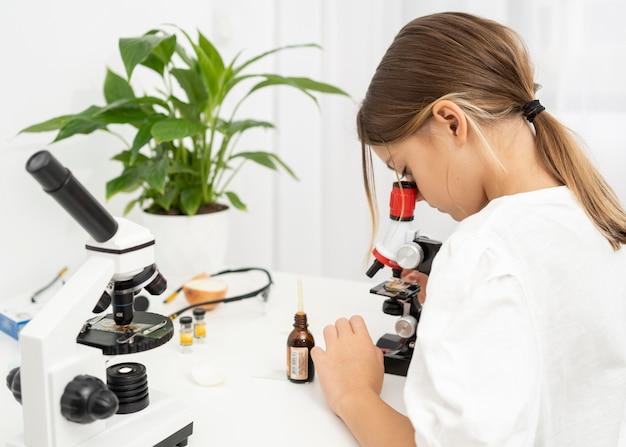 Вид сбоку девушки, смотрящей в микроскоп