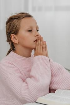 Девушка молится с библией, вид сбоку