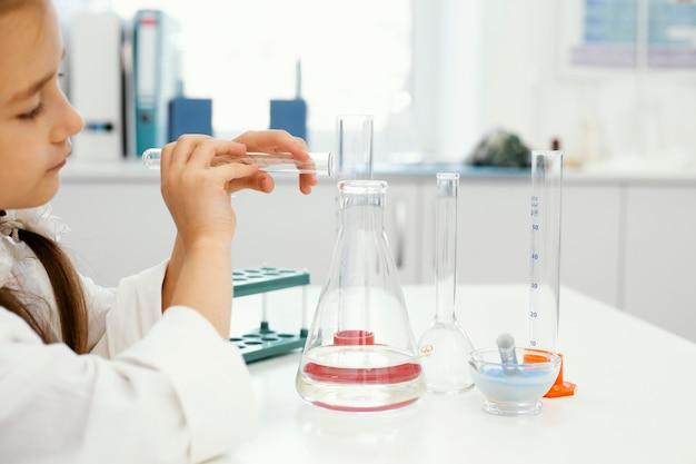 테스트 튜브 실험과 실험실에서 여자 과학자의 측면보기