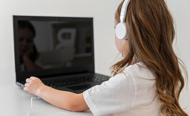 ヘッドフォンでラップトップを使用して女の子の側面図