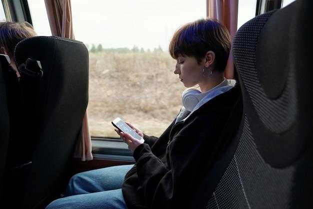 Девушка со смартфоном сидит у окна в автобусе, вид сбоку