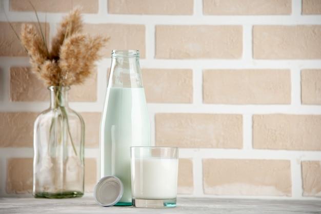 파스텔 색상 벽돌 배경의 오른쪽에 우유 캡으로 채워진 유리 병 및 컵의 측면 보기