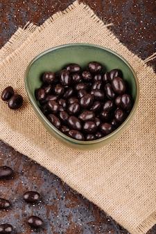 Вид сбоку глазированные шоколадные ореховые конфеты в миску на вретище на деревенском фоне
