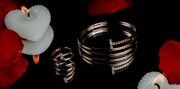 Вид сбоку позолоченного браслета и кольца с кристаллом на черном столе