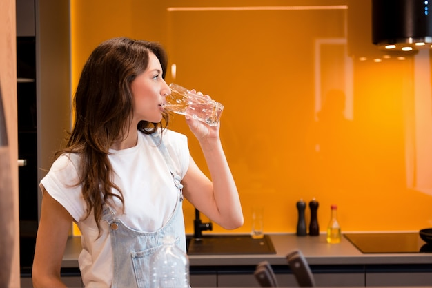 キッチンのガラスから新鮮な水を飲む黒髪のハンサムな女性の側面図