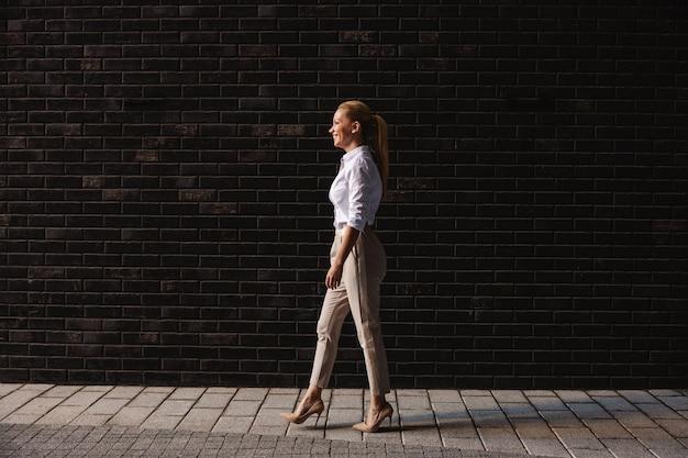 通りを歩いているゴージャスな金髪のファッショナブルな実業家の側面図。