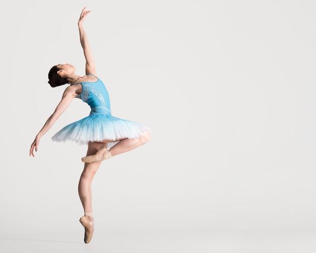 Вид сбоку грациозных балерина танцует с копией пространства