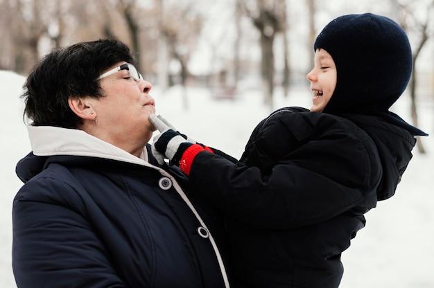 Бабушка и внук на открытом воздухе, вид сбоку