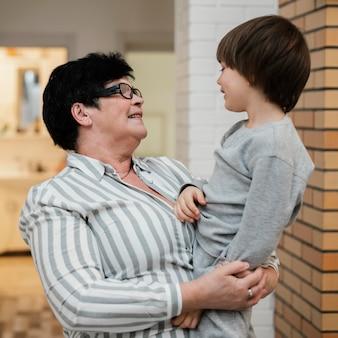 Бабушка держит внука, вид сбоку