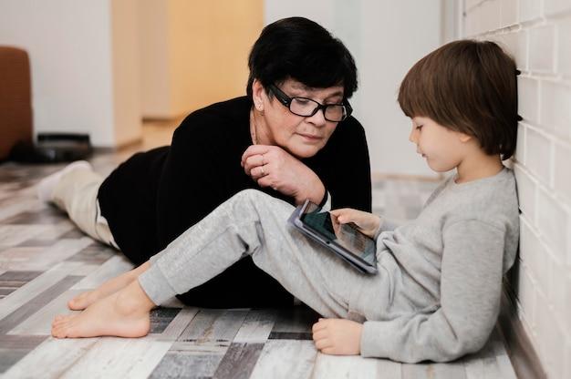 Вид сбоку внука, играющего на планшете с бабушкой