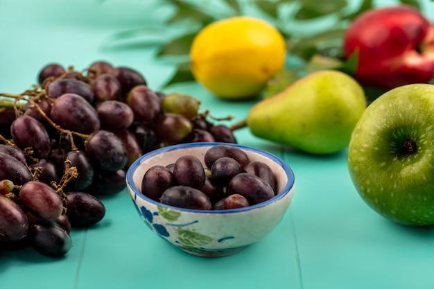Вид сбоку виноградных ягод в миске и виноградного яблока с грушей, персиком и лимоном на синем фоне
