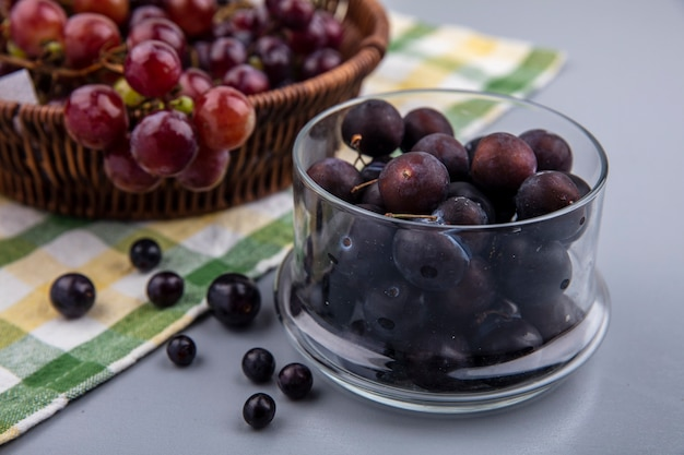 灰色の背景の格子縞の布にブドウのバスケットとガラスのボウルにブドウの果実の側面図