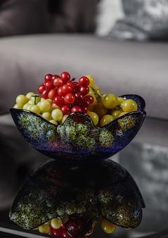 テーブルの上のガラスの花瓶のブドウの側面図